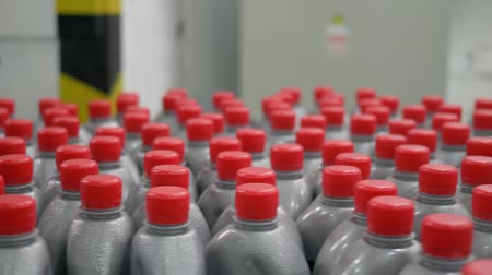 identical : plastic gray bottles with red lids filled with liquid, move in a circle on conveyor belt indoors at plant Stock Footage