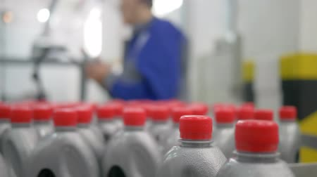 lids : machine oil factory, plastic bottles in grey with red lids move in a circle on conveyor belt indoors near the worker