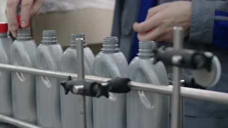lids : plant of machine oil, worker closes lids on grey plastic bottles moving on a conveyor line close up