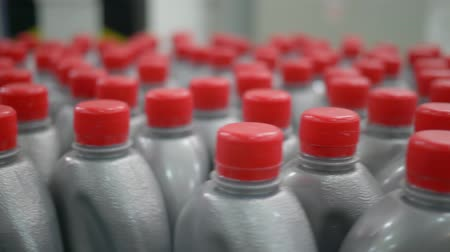 fedél : plastic bottles in grey with red lids filled with liquid, move in a circle on conveyor belt indoors at factory Stock mozgókép