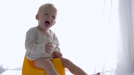 loo : cheerful healthy kid boy sitting on potty and sticks fingers in mouth in bright room close-up Stock Footage