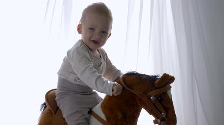 lugares sentados : early childhood, happy kid boy swinging on toy horse at home close-up Stock Footage