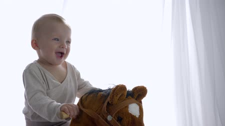 assentos : emotion joy of child, cheerful baby boy relish riding on toy equine in room close-up Stock Footage