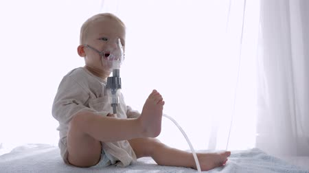 compressore : inhalation procedure, lovely toddler boy breathes via nebulizers for Treats inflammation of airways in bright room close up