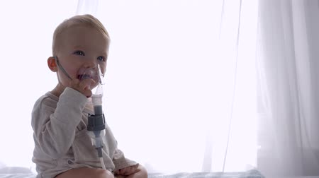 diseased : prevention of cough, cute infant boy breathes via Inhalers Compressor for Treats inflammation of airways in bright room close up Stock Footage