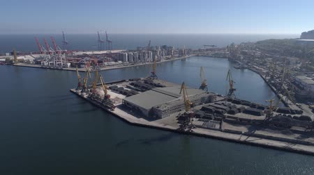 moorage : Aerial View of Industrial trading port with containers and lifting cranes for loading and unloading of vessel on Sea coast against blue sky and water