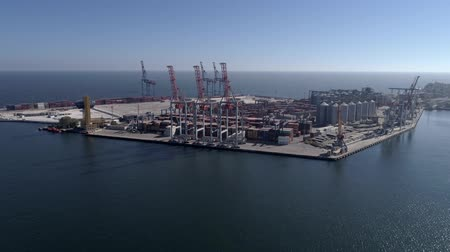 moorage : Commercial port with container and lifting cranes for loading and unloading of vessel on Sea waterfront against blue sky and shiny water, bird eye view