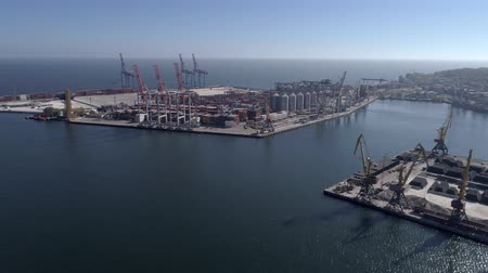 unload : Flying above Industrial trading port with grain storage elevator with containers and lifting cranes for loading and unloading of vessel on Sea Embankment against blue sky and shiny water, aerial view