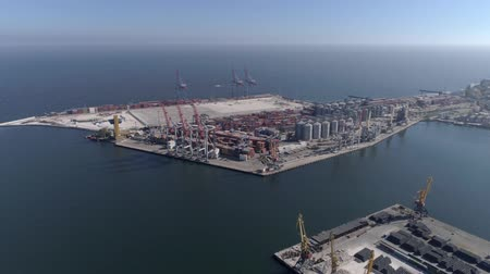 moorage : Industrial sea wharf with containers with grain storage elevator and lifting cranes for loading and unloading of vessel on Sea shore, aerial view