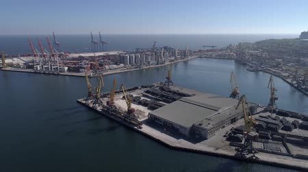 moorage : marine industry, aerial survey of trading port with containers with grain storage elevator and lifting cranes for loading and unloading of vessel on Sea shore against blue sky and shiny water