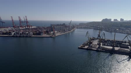 moorage : port industry, drone view of trading sea harbor with containers with grain storage elevator and lifting cranes for loading and unloading of ships on Sea coast against blue sky and shiny water Stock Footage