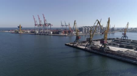 moorage : sea industry, commercial berth with containers and lifting cranes with grain storage elevator on Sea coast against blue sky and shiny water, aerial view Stock Footage