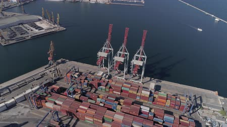 moorage : ODESSA, UKRAINE - OCTOBER 17, 2018: Industrial merchant port with containers and lifting cranes for loading and unloading of vessel on Black Sea shore, aerial view