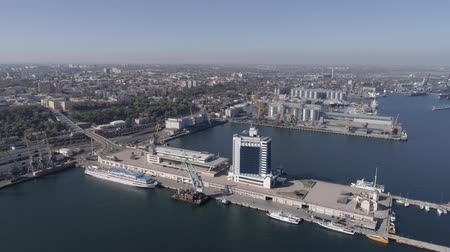 moorage : ODESSA, UKRAINE - OCTOBER 17, 2018: panorama of city international port with hotel and vessel on Black Sea shore against blue sky, aerial survey