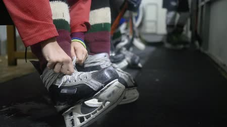 desfocado : hockey player tying shoelace on skating and ready to go on rink, close-up on unfocused background Vídeos