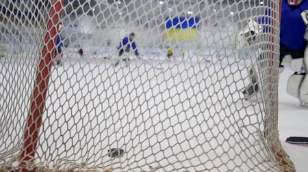 striker : KHERSON, UKRAINE - OCTOBER 17, 2018: goalkeeper in hockey suit stands at gate and catches puck from opponent at ice rink during competition, goal close-up