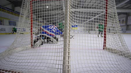 вратарь : KHERSON, UKRAINE - OCTOBER 17, 2018: hockey goal, goalkeeper into sports clothes with hockey stick fails and missed puck into goal from opponent on ice rink