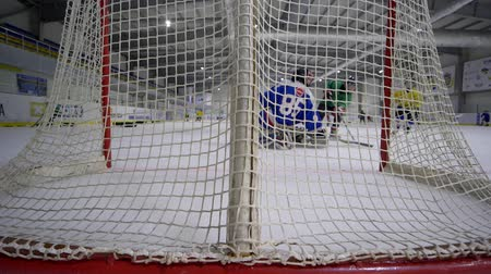 top sürme : KHERSON, UKRAINE - OCTOBER 17, 2018: hockey match, goalie with hockey stick falls and missed puck from opponent into goal on ice rink