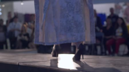 semana de moda : catwalk defile, model in high heels and clothes of new collection walking on runway during fashion week in unfocused