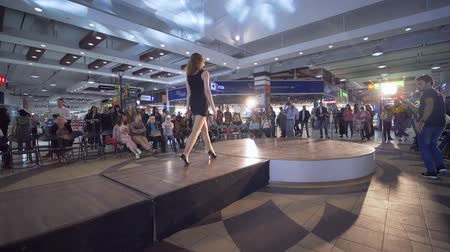 зрителей : KHERSON, UKRAINE - OCTOBER 20, 2018: Defile show, slim model girl into in black cocktail dress and high heels go on Catwalk during presentation of new collection clothes at fashion Week Стоковые видеозаписи