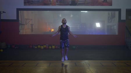 skákání : KHERSON, UKRAINE - OCTOBER 10, 2018: healthy young boxer man jumping rope on the background of a large mirror in a dark gym during training