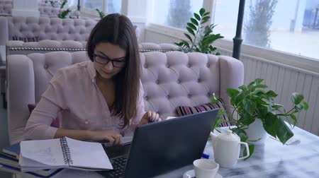 correspondência : modern computer technology in distance education, happy student girl working with laptop to learn from online lessons and making notes in notebook close-up Stock Footage
