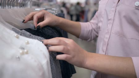péntek : arms of customers girl considering new fashion clothing on hangers in shop during sales discounts, hands close up on unfocused background Stock mozgókép