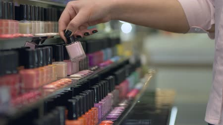 vernik : buyer Girl chooses nail polish for manicure and pedicure from large number of bottles of nail varnish on shop showcase, hands close-up Stok Video
