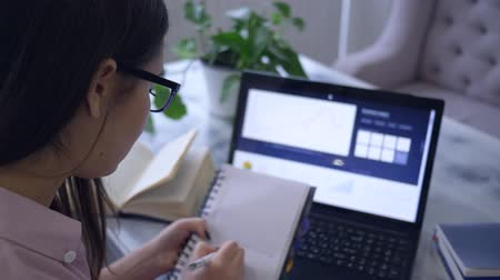 netbook : remote online learning, student girl working with laptop device and draws a graph in notepad sitting at a table in cafe Stock Footage