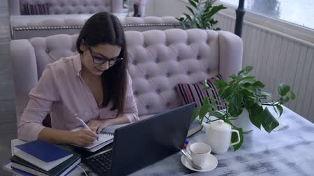 netbook : student girl in eyeglasses using laptop writes notes with pen in notebook sitting at a table during e-education in cafe