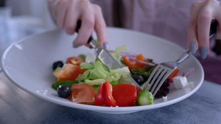 dietético : beautiful diet food, female hands with a knife and fork cut the fresh cucumber in a Greek salad closeup Stock Footage
