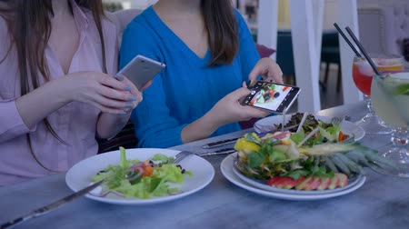 bloggers : blogging, hands of female friends take pictures of beautiful useful food on mobile phone during breakfast during diet for weight loss in cafe close-up