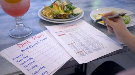 liste : diet, nutritionist girl is looking for in the list of fruits and their calories near punch and healthy vegan food in plate at cafe