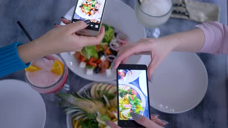 obesity : blogging, smartphone in hand girlfriends makes photo of useful vegetarian food during breakfast for social media in restaurant, close up on unfocused background Stock Footage