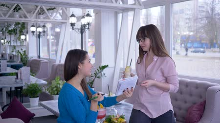 dietético : eating plan, young women with the aim to lose weight writes down healthy vegetable diet together in a cafe Stock Footage