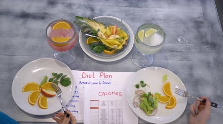 きちんとした : fitness diet, girls eat the vegetable and the fruit from plates sitting at the table with calories table and diet plan