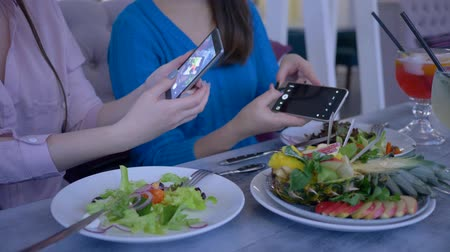 dietético : food photo on smartphone, bloggers girls take pictures of beautiful useful eating on cell phone during brunch during diet for weight loss in cafe close-up Stock Footage