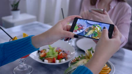 dietético : food photo, arm of girl using mobile phone for pictures of vegetarian meal during healthy breakfast for social media in restaurant, close-up Stock Footage