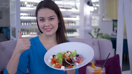 fortunate : happy diet, healthy smiling girl eats useful beautiful food from vegetables for weight loss in restaurant and gives thumb up in restaurant