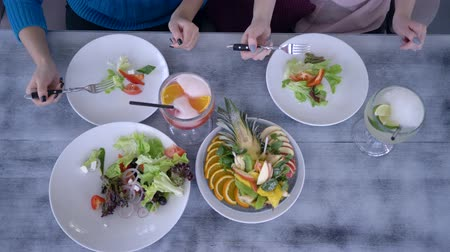 dietético : healthy food and fruit juice in glasses on table, girls hold in hands forks and eats greek salad from plates
