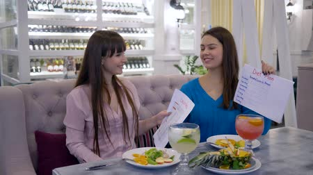 dietético : healthy lifestyle, beautiful girls holding in hand calories list and diet plan smiling on camera in cafe