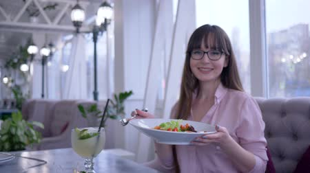 görög : healthy lifestyle, girl with long hair in eyeglasses with a fork and plate in hand eating Greek salad and looking at the camera Stock mozgókép