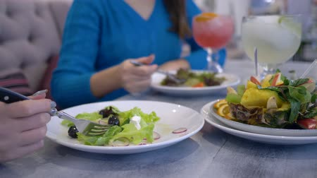 overweight : healthy lifestyle, girls on a diet eats greek salad from white plates sitting at the table in cafe