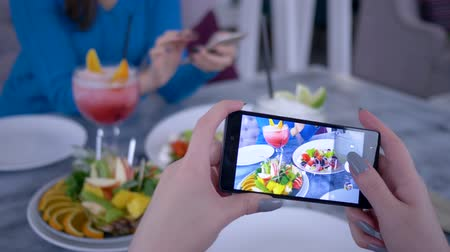 desfocado : modern technology in action, cell phone in girl hand take pictures healthy vegetarian food during dinner for social networks in restaurant, close up on unfocused background Vídeos