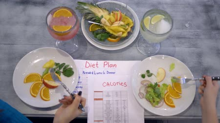 overweight : healthy vegan food, girls eat the fruit from plates sitting at the table with calories table and diet plan Stock Footage