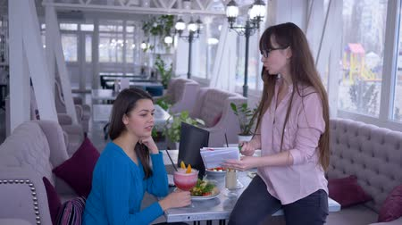 dietético : meal plan, girl in glasses offers vegetables diet for girlfriend during healthy breakfast in a cafe Stock Footage