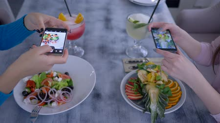 dietético : slimming food, girlfriends on smartphone taking pictures of vegetable and fruit salad for social media during healthy brunch in cafe close up Stock Footage
