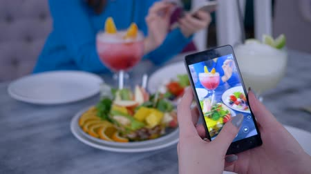 desfocado : smart telephone in blogger woman hand makes photo healthy vegetarian eating during lunch for social networks in restaurant, close up on unfocused background Vídeos