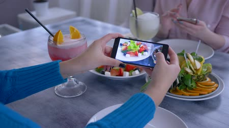 dietético : useful low calorie food, arm of blogger woman using cell phone for photo of vegetarian eating during healthy lunch for social networks in restaurant, close-up Stock Footage