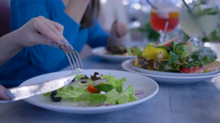 dietético : vegetable diet nutrition, hands closeup eating healthy salad from plate during useful dinner in cafe close-up Stock Footage